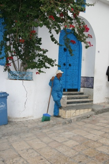 Colour-co-ordinated worker in the village of Sidi Bou Said overlooking the Bay of Tunis